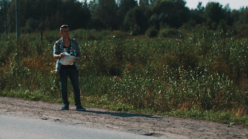 Young Boy Hitchhiking at Roadside