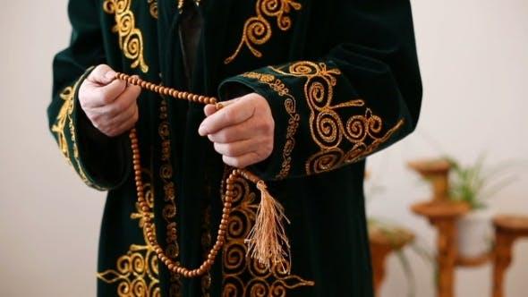 Thumbnail for Ein alter Mullah in Nationalkleid betend mit Rosenkranz Perlen in Händen