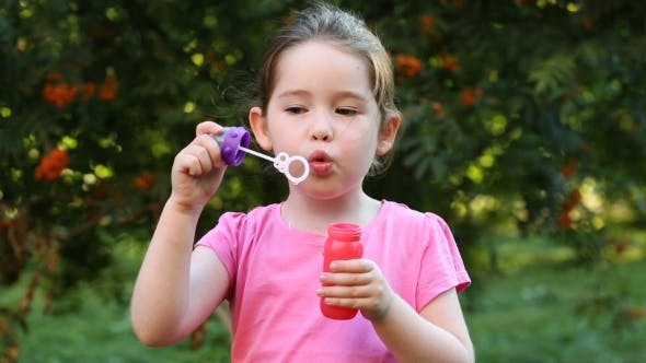 Cover Image for Happy Child Blowing Soap Bubbles In Park