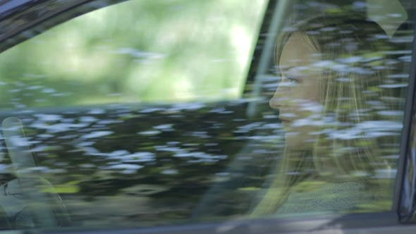 Thumbnail for Smiling Female Driver Opening Car Window