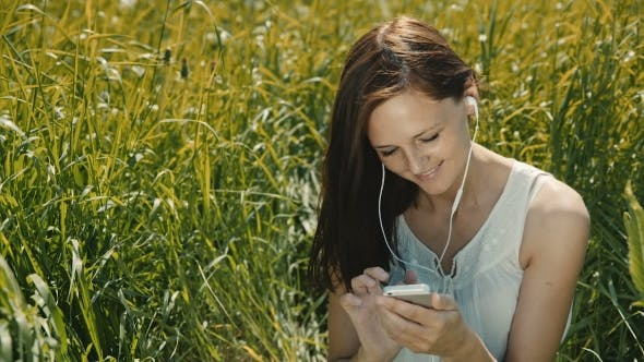 Thumbnail for Happy Woman Listening To Music And Using Smartphone In The Park