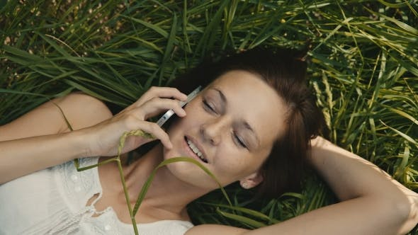 Thumbnail for Beautiful Woman Lying On The Grass Talking On The Phone And Smiling