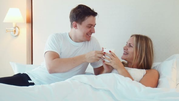 Thumbnail for Man Bring a Cup Of Tea Or Coffee To Woman Sleeping In Bed