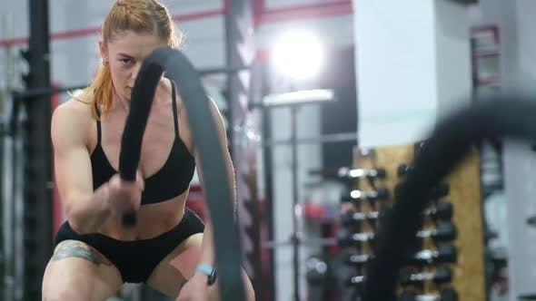 Athlete training in the gym, holding a crossfit with battle ropes.