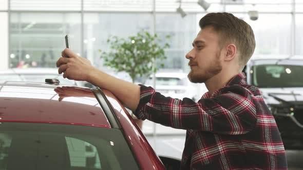 Thumbnail for Fröhlicher Mann mit Smartphone zeigt Autoschlüssel an die Kamera posiert bei der Händlerschaft