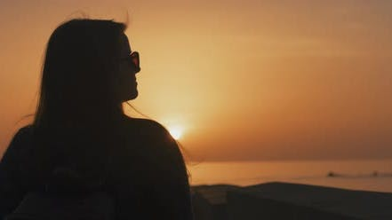 Silhouette of a young woman at sunset
