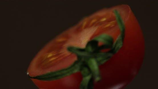 Thumbnail for Drehen der Hälften der frisch reifen Tomate auf dunklem Hintergrund