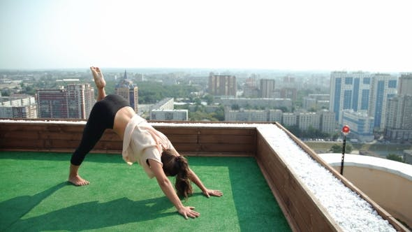 Thumbnail for Yoga And Meditation In a Modern City. Young Woman Doing Yoga On The Roof. 20S.