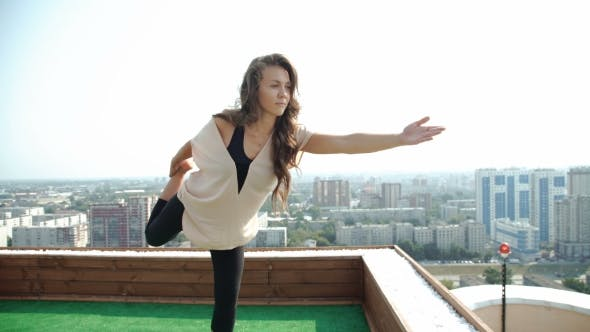 Thumbnail for Young Woman Doing Yoga On The Mat On The Roof, Sitting In Lotus Posture