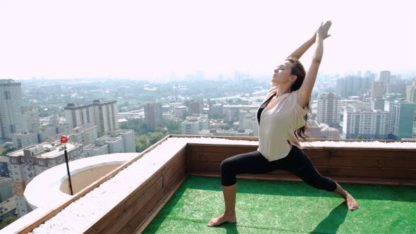 Thumbnail for Young Woman Doing Yoga On The Mat On The Roof