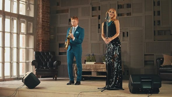 Thumbnail for Jazz Vocalist in Glowing Dress and Saxophonist in Blue Suit Perform on Stage.