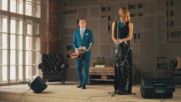 Thumbnail for Jazz Vocalist And Saxophonist In Blue Suit Perform On Stage. Elegantly Duet.