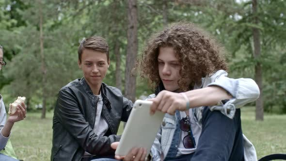 Thumbnail for Teens Resting in Park and Using Digital Tablet