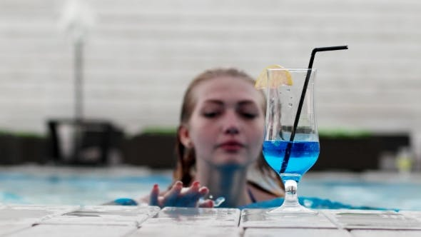 Thumbnail for A Girl Swims To The Blue Alcoholic Cocktail