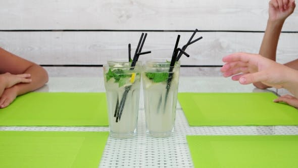 Cover Image for Female Hands Taking a Refreshing Mojito Cocktails