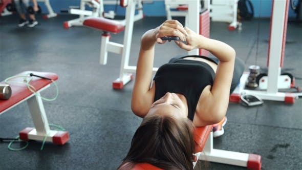 Thumbnail for Young Sports Woman Using Phone Lying On The Training Apparatus In The Gym