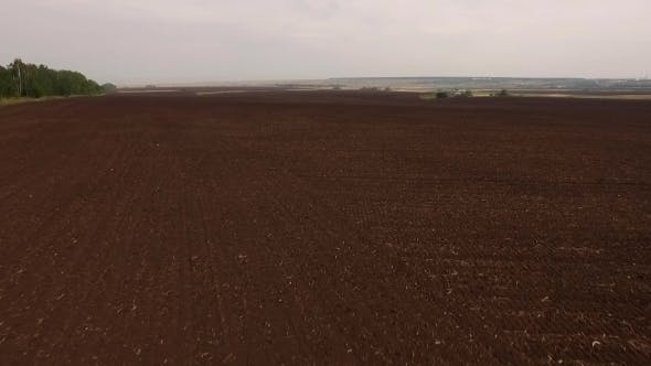 Thumbnail for Drone Flying Up Over Black Plowed Field, Rising High And Showing Beautiful Countryside Landscape