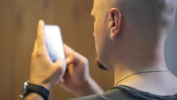 Thumbnail for Bald Person With Beard Types Text Messages On Smartphone.