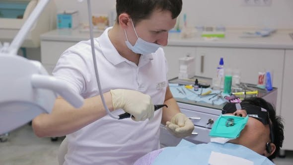Thumbnail for Young Stomatologist Sits Near Patient In Working Cabinet
