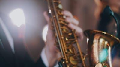 Saxophonist In Dinner Jacket Perform On Stage. Spotlight. Golden Saxophone. Jazz