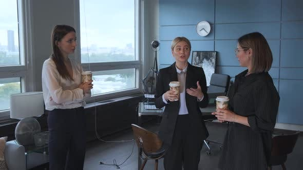 three businesswomen enjoy the girls talk in the office and drinking coffee together at afternoon