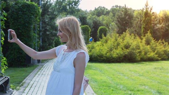 Thumbnail for Beautiful Girl Making Selfie Enjoying the Sun in City Park 3