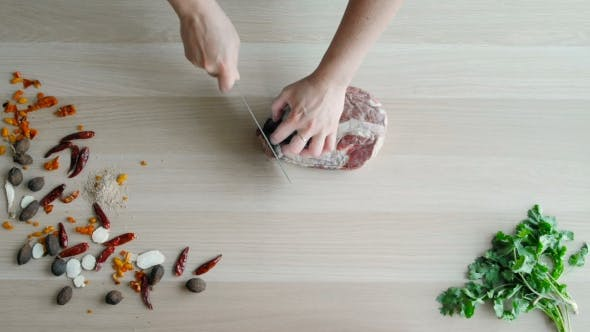 Thumbnail for Raw Meat Slices Cutted on Wooden Board. Top View of Chefs Hands Chopping Beaf