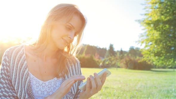 Thumbnail for Happy Smiling Girl Using a SmartPhone in City Park Sitting on Grass 1