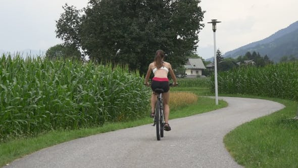 Young Girl Riding Bicycle On Rural Road