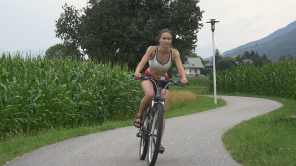 Fit Woman Cycles Along The Bike Trail
