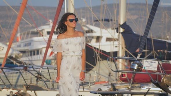 Thumbnail for A Beautiful Sexy Woman Walking At a Port And Smiling Thinking About The Happy Moments