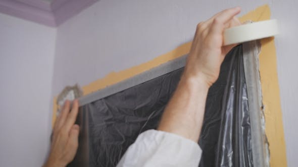 Cover Image for Worker Protecting Batten Moulding With Masking Tape Before Painting At Home Improvement Work.
