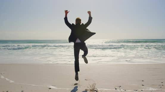 Thumbnail for Businessman jumping on beach in the sunshine