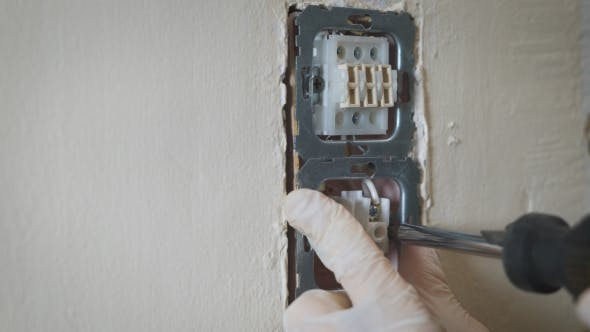 Changing Room Wall Light Switch Installation With a Screwdriver,  Electrician Hands.