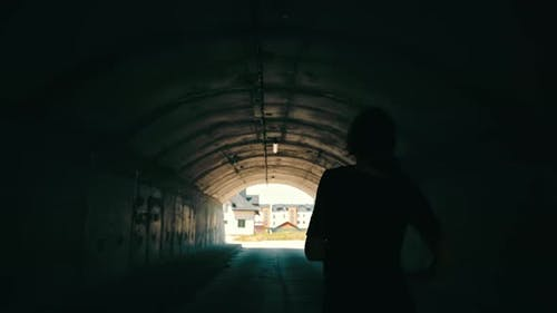 Woman Runs to the Light at the End of the Tunnel
