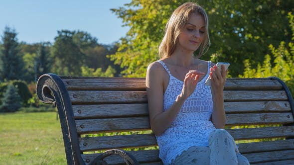 Cover Image for Happy Smiling Girl Using SmartPhone in City Park Sitting on the Bench