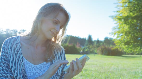Thumbnail for Happy Smiling Girl Using a SmartPhone in City Park Sitting on Grass