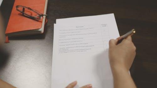 Frauenhand in einem Business-Anzug unterzeichnet Dokumente. Die Jury legt die Schätzung.