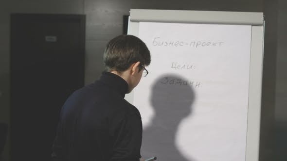 Young Man Making a Presentation About The Flip-chart.