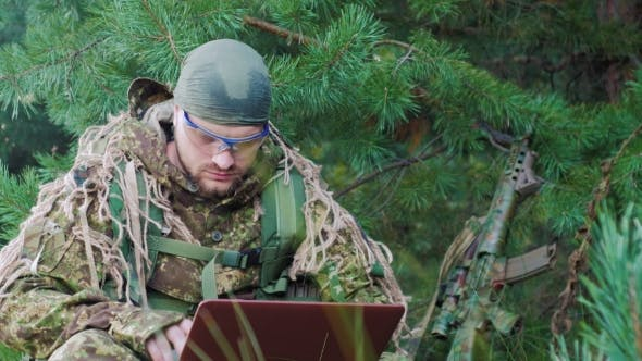 Thumbnail for Portrait Of Military Man Sitting In The Woods, Dressed In Camouflage. It Uses Laptop