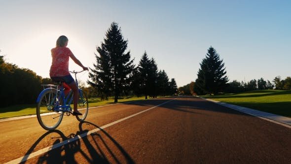 Thumbnail for Young Woman Riding a Bicycle In The Sunset