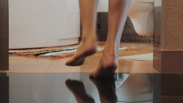 Thumbnail for Woman With Bare Legs Walk Into Bathroom Come To White Bath. Little Carpet.