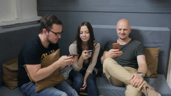 Thumbnail for Three Friends Sit On Sofa In Studio And Play With Smartphones.
