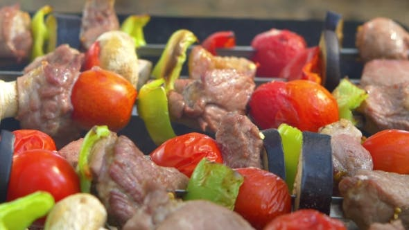 Thumbnail for Man Turns Two Skewers Kebabs, Barbeque Put On Brazier