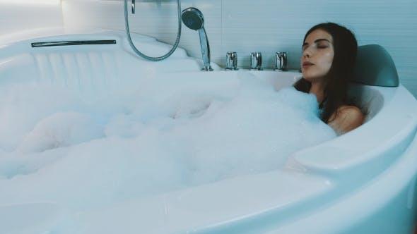 Thumbnail for Young Brunette Girl Taking Bath Full Of Foam In Bathroom