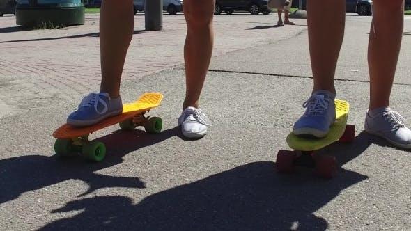 Thumbnail for Teenage Couple Feet Riding Short Modern Skateboard