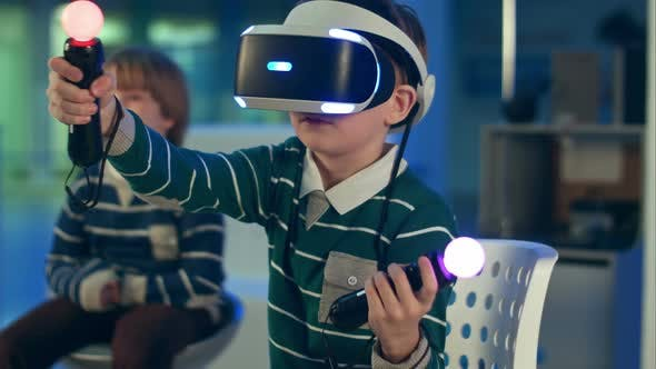 Cover Image for Little Boy in Vr Headset Playing Virtual Reality Game with Controllers While Another Boy Waiting for
