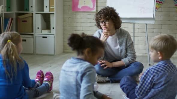Female Teacher Speaking with Children in Kindergarten