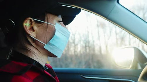 Young Lady Wearing Protective Mask to Prevent Spreading COVID19 in Car