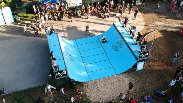 Thumbnail for Male skateboarder doing tricks in an outdoor mini-ramp contest.